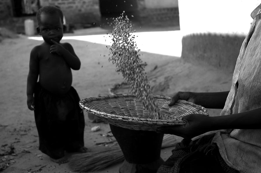 A little girl watches her mother seive grain. Her mother recently returned from the jungle having been abducted by the LRA. Luckily she was accepted back into a family in Achet. She has since married and ex LRA rebel who also escaped.