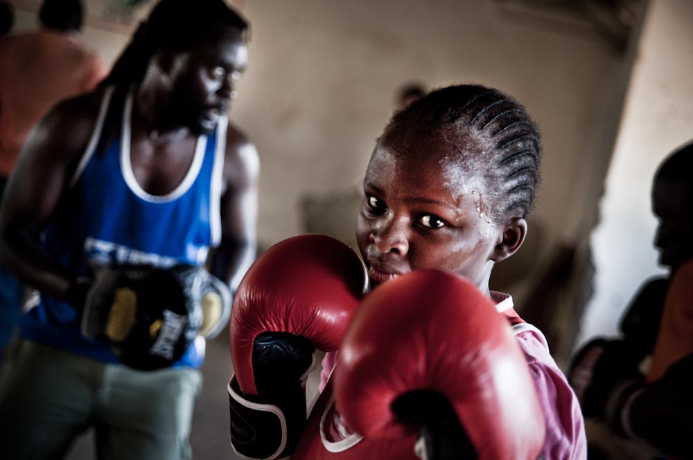 At 13, Tabitha Njeri will lead the 'Life Skills' classes after training has finished. Amongst many things, 'Life Skills' involve confidence building, sexual health education and gender role debates. Priest, her boxing teacher, mentor and trainer spas in the background.