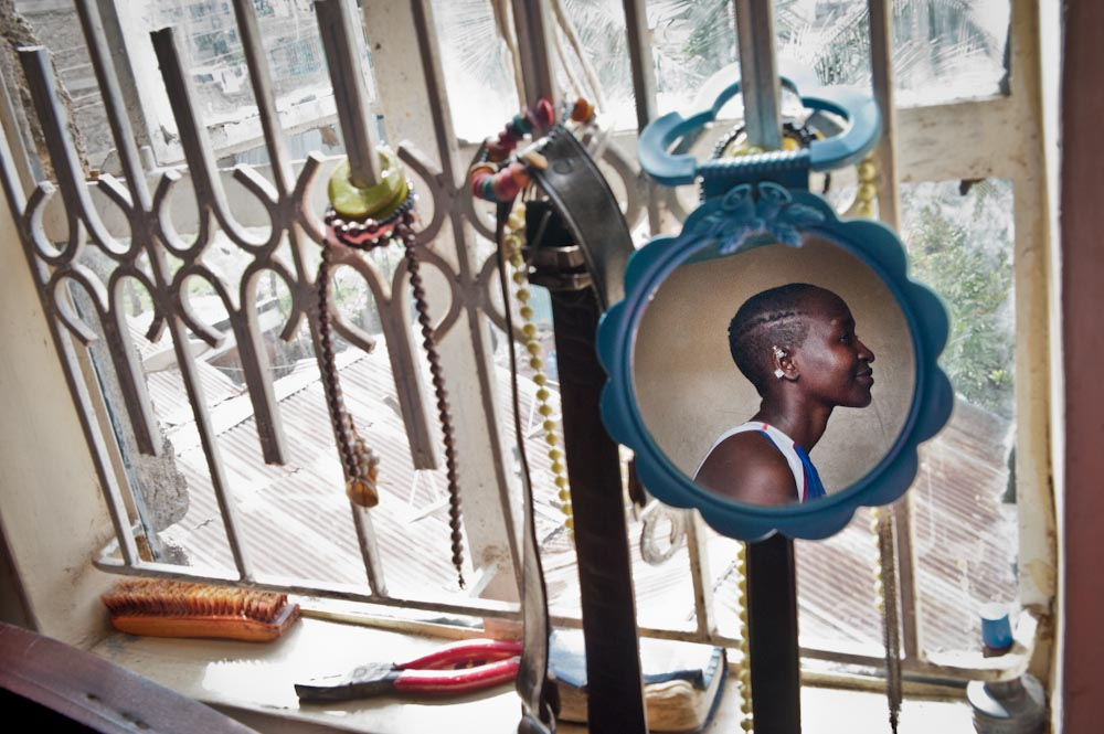 A portrait of Sonko in her bedroom as her fashion accessories hang off the burglar bars. Sonko shares 1 bed with her two younger sisters in Nairobi's Eastlands slum area.