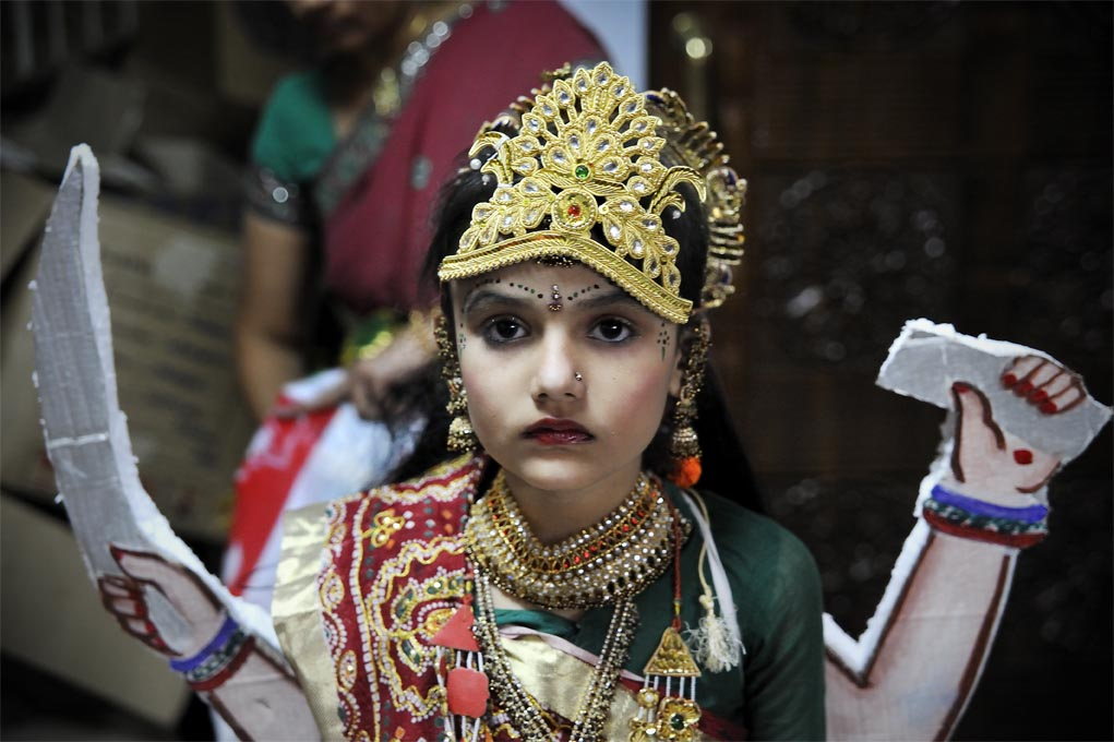 Along side the worship, various socio-religious functions take place, such as competitions for the best dancer or the best dressed individual. A girl stands to be judged for 'the best dressed, goddess' at Jalaram Temple Nairobi.