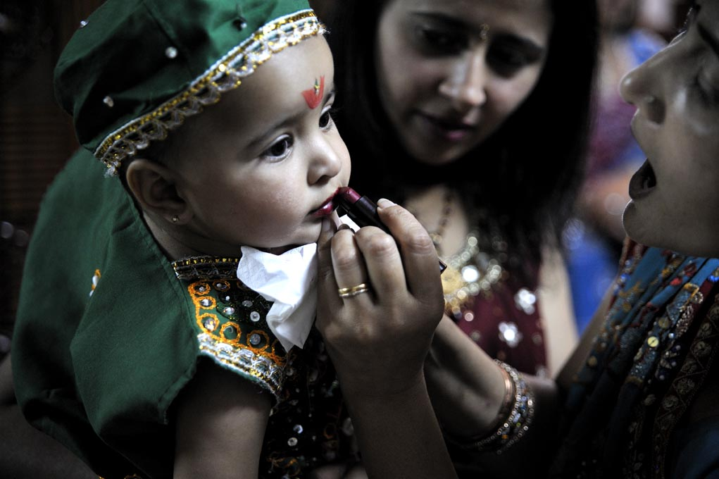 Along side the worship, various socio-religious functions take place, such as competitions for the best dancer or the best dressed individual.Here a baby is made up for the competition.