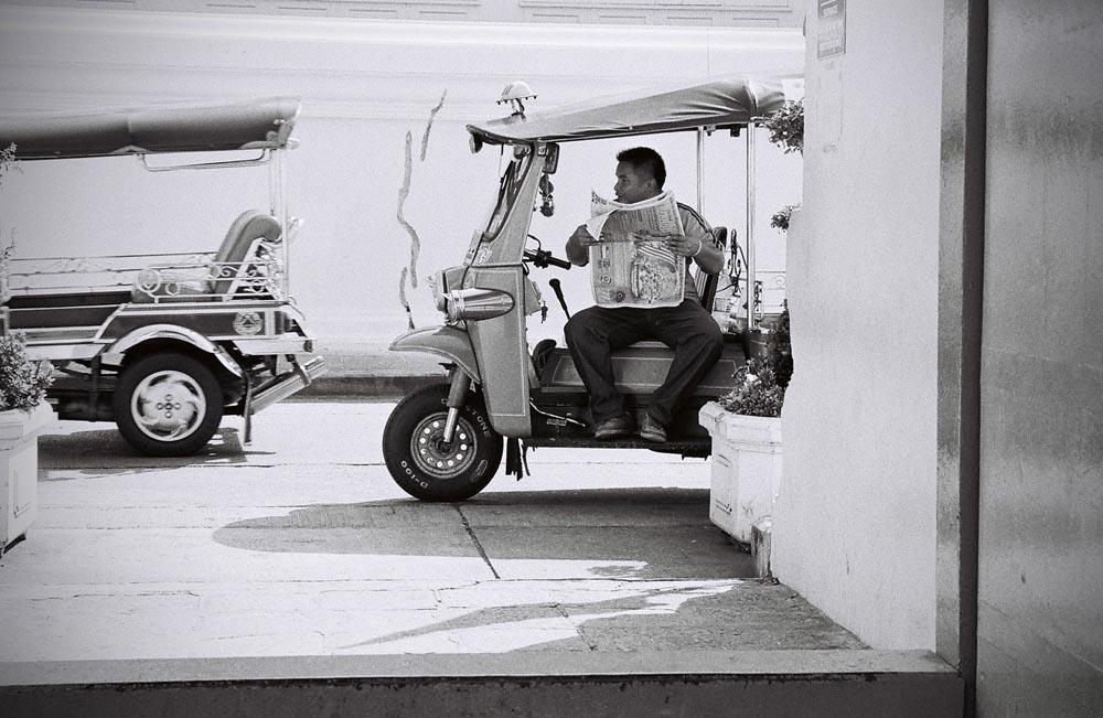 A tuk tuk driver waits to pick up tourists outside Wat Mahathat