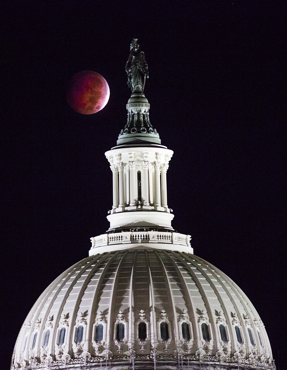 A full total lunar eclipse of the moon is visible over the dome of the United States Capitol in Washington.  A {quote}blood moon{quote} occurs when the earth positions itself between the sun and the moon, creating a full lunar eclipse with a majestic red hue.