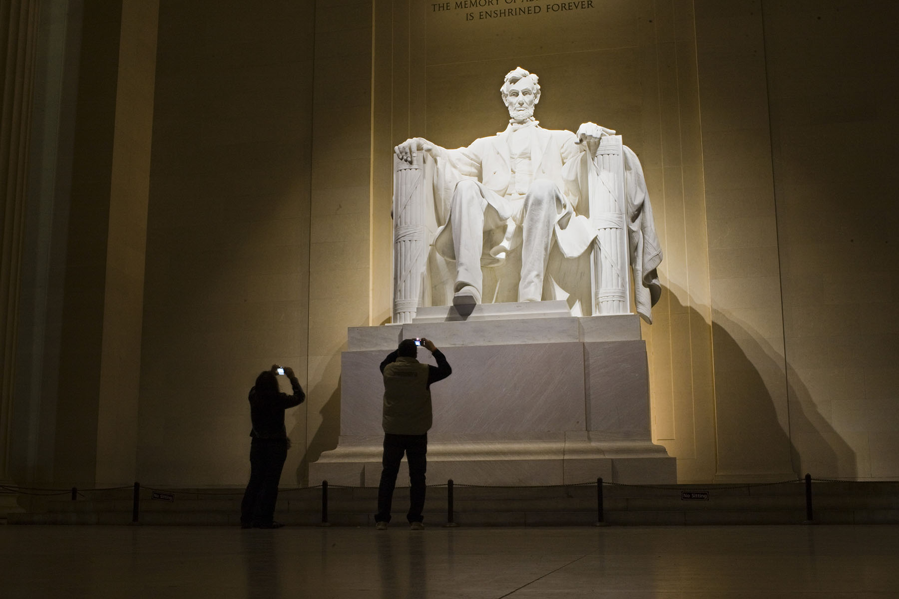 Tourists inside the Lincoln Memorial,  built to honor the 16th President of the United States, Abraham Lincoln.  It is located on the National Mall in Washington, D.C. Photo by Brooks Kraft/Corbis