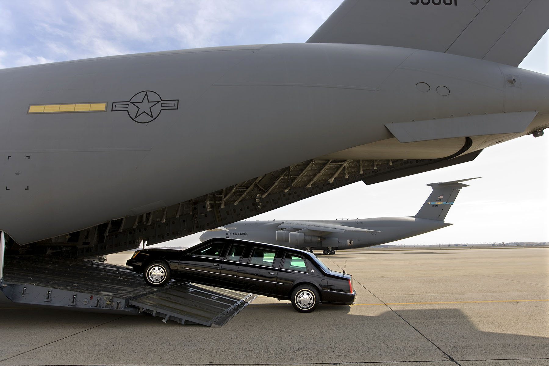 A Presidential limousine is loaded onto a C5 military transport plane bound for eastern Europe, where President Bush is headed next week.  A {quote}secure package{quote} of motorcade vehicles, including the limousines and a fleet of Secret Service SUVs is transported to the site of every presidential visit. Photo by Brooks Kraft/Corbis