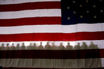 Supporters sit in front of an AMerican flag while listening to President George W. Bush speak at a Republican Party congressional mid-term election campaign rally in Bentonville, Arkansas, November 6, 2006.Photo by Brooks Kraft/Corbis
