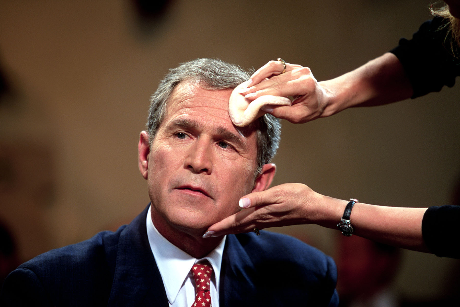 Republican presidential candidate George W Bush gets make up put on before a television interview.
