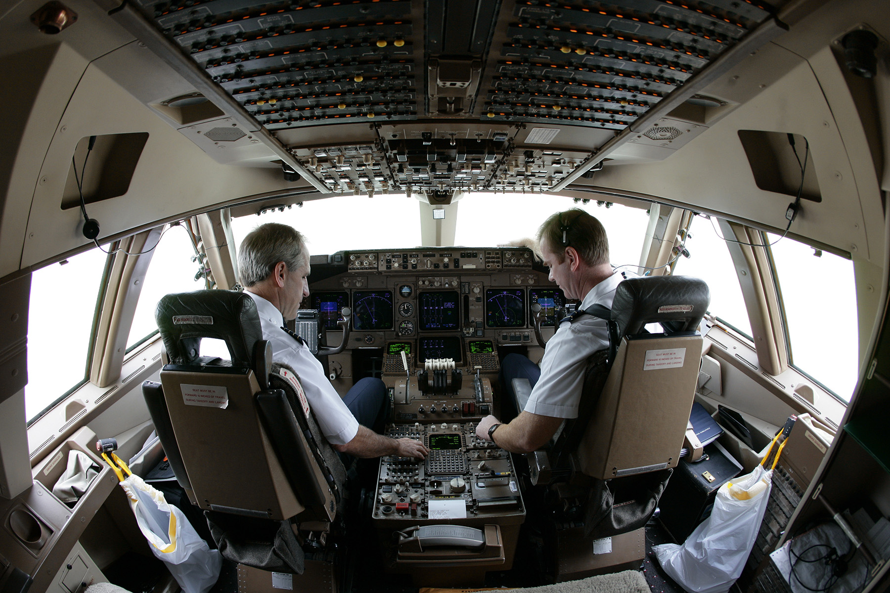 Pilots fly inside the cockpit of a commercial passenger 747-400 airplane.Photo by Brooks Kraft/Corbis