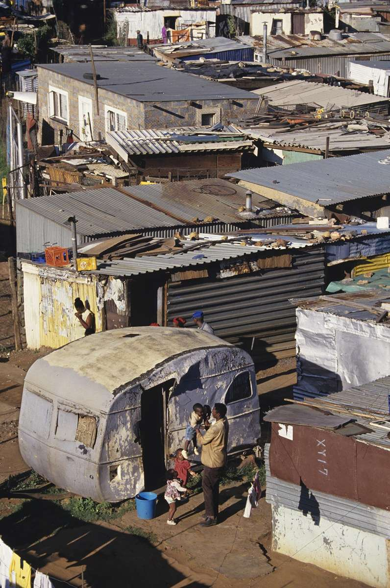 A family outside shanty homes in Soweto,  an urban area of the city of Johannesburg, South Africa.  Its origins are as a very poor and impoverished black township under South Africa's Apartheid government. The population has historically been overwhelmingly black and some of the watershed events in the struggle against Apartheid occurred in the township.