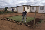 A man plants gras around shanty homes in Soweto,  an urban area of the city of Johannesburg, South Africa.  Its origins are as a very poor and impoverished black township under South Africa's Apartheid government. The population has historically been overwhelmingly black and some of the watershed events in the struggle against Apartheid occurred in the township.