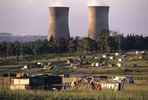 A nuclear power plant looms behind shanty homes in Soweto,  an urban area of the city of Johannesburg, South Africa.  Its origins are as a very poor and impoverished black township under South Africa's Apartheid government. The population has historically been overwhelmingly black and some of the watershed events in the struggle against Apartheid occurred in the township.