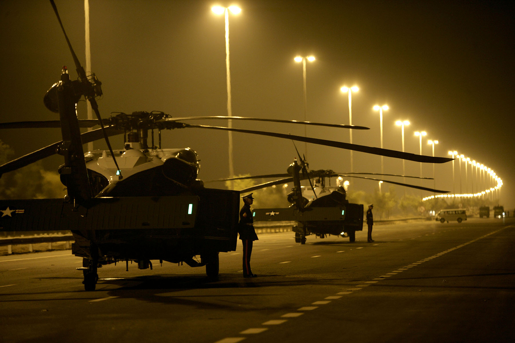 Marines wait for the arrival of U.S. President George W. Bush as two Marine One helicopters are parked on a closed-off road near Sowaihan in the United Arab Emirates January 13, 2008. Bush was the guest of honor at a dinner hosted by Abu Dhabi Crown Prince Sheikh Mohammed Bin Zayed Al Nahyan at his desert retreat. Photo by Brooks Kraft/Corbis
