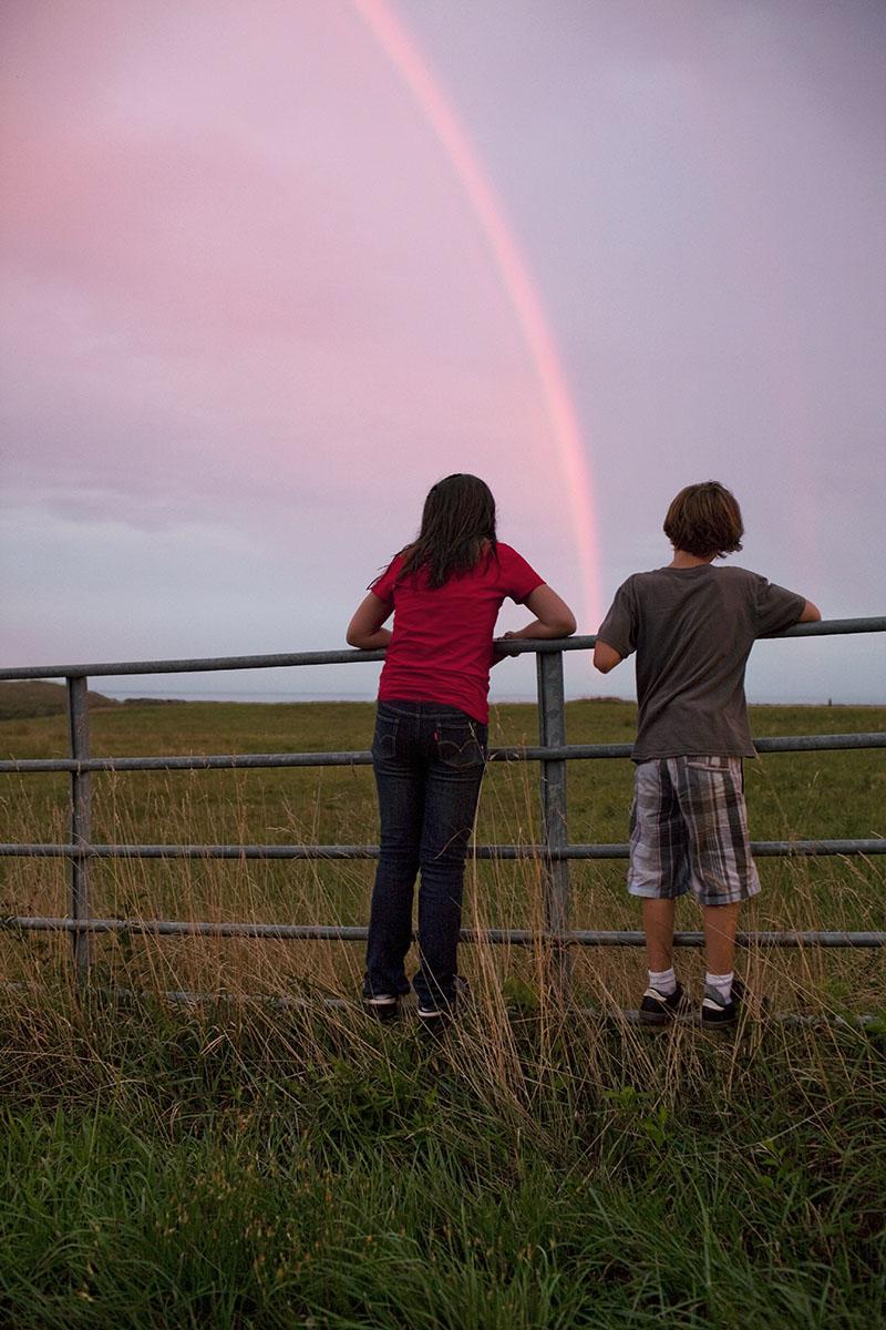 Children watch a rainbow over a farm field on the island of Martha's Vineyard, MA.