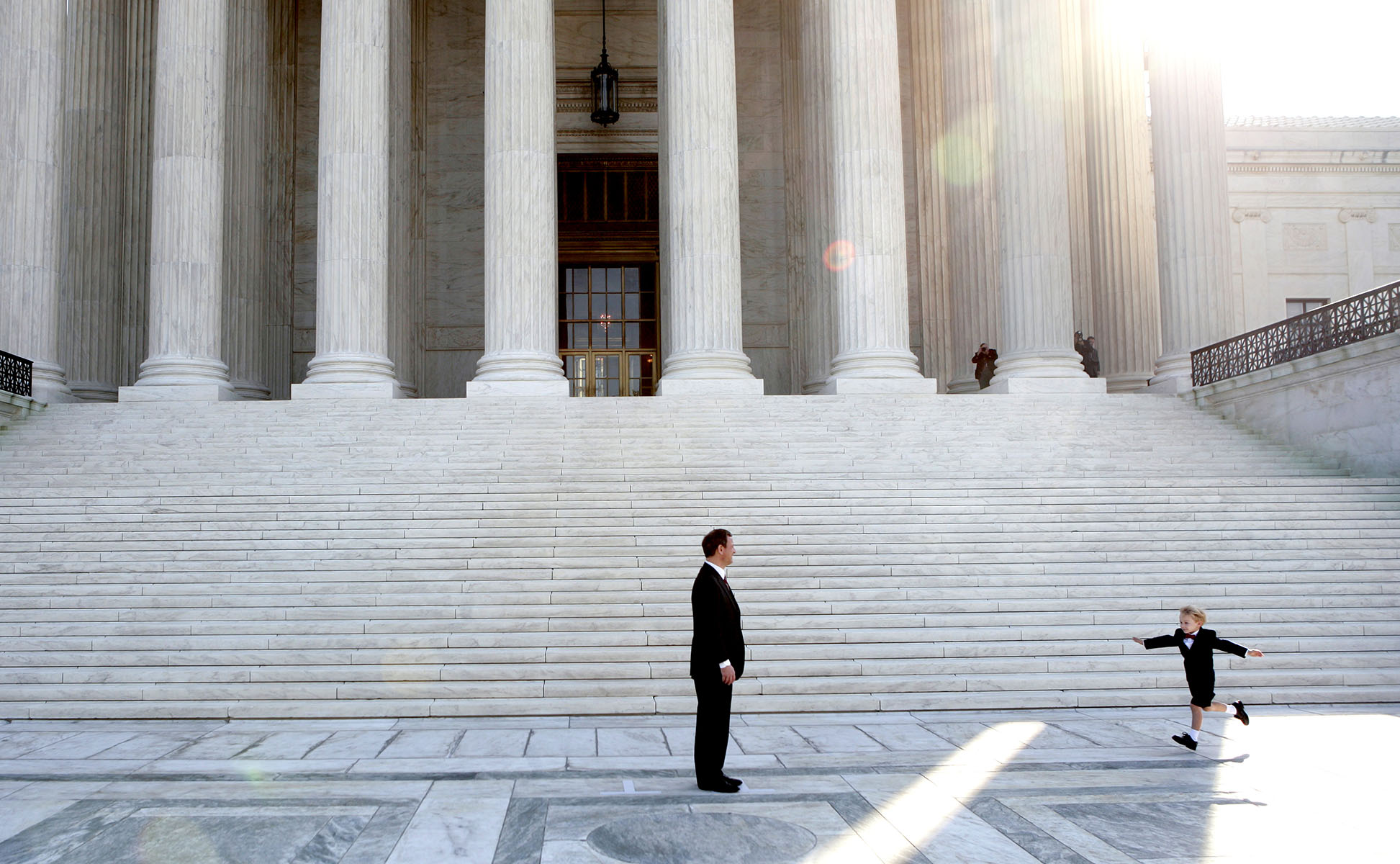 U.S. Chief Justice John Roberts (L) reaches for his son, Jack, 4, on the steps of the Supreme Court after his investiture ceremony inside the Supreme Court in Washington D.C. October 3, 2005.Photo by Brooks Kraft/Corbis