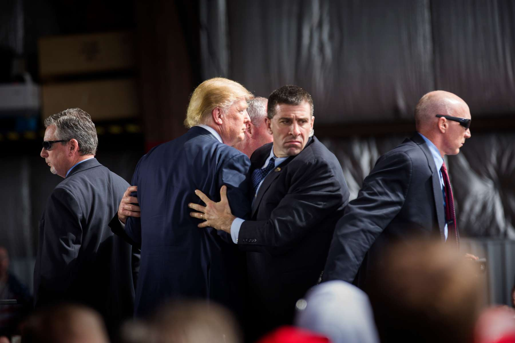 DAYTON, OH - MARCH 12: Republican presidential candidate Donald Trump is surrounded by Secret Service agents during a campaign event on March 12, 2016 in Dayton, Ohio.  The agents were responded to a protestor that had rushed the stage while Trump was speaking.  (Photo by Brooks Kraft/Getty Images)