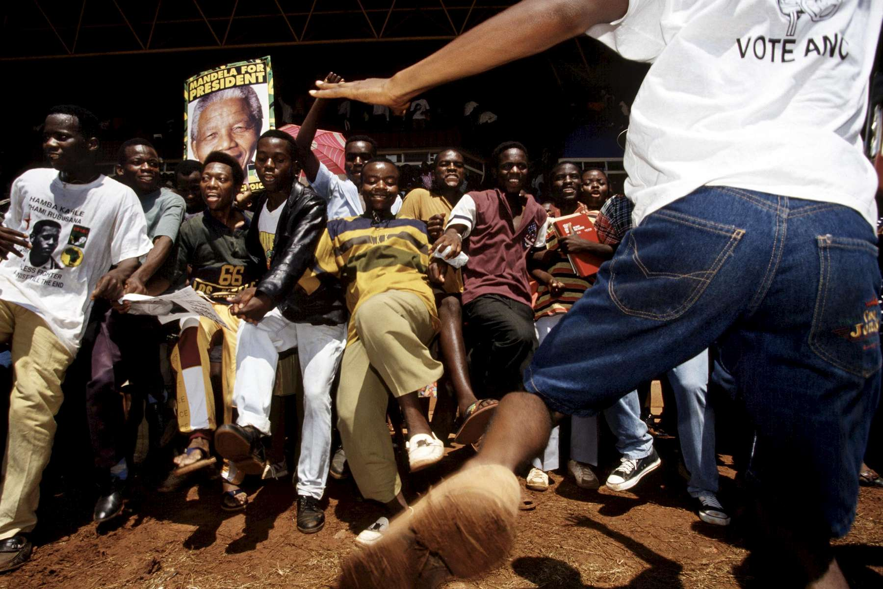 Crowds dance at a Nelson Mandela campaign event.  After more then 27 years in jail as an anti-apartheid activist,   Nelson Mandela lead a 1994 campaign for President as a member of the African National Congress (ANC),  in the first free elections in South Africa in 1994.  Mandela has received more than 250 awards over four decades, including the 1993 Nobel Peace Prize.