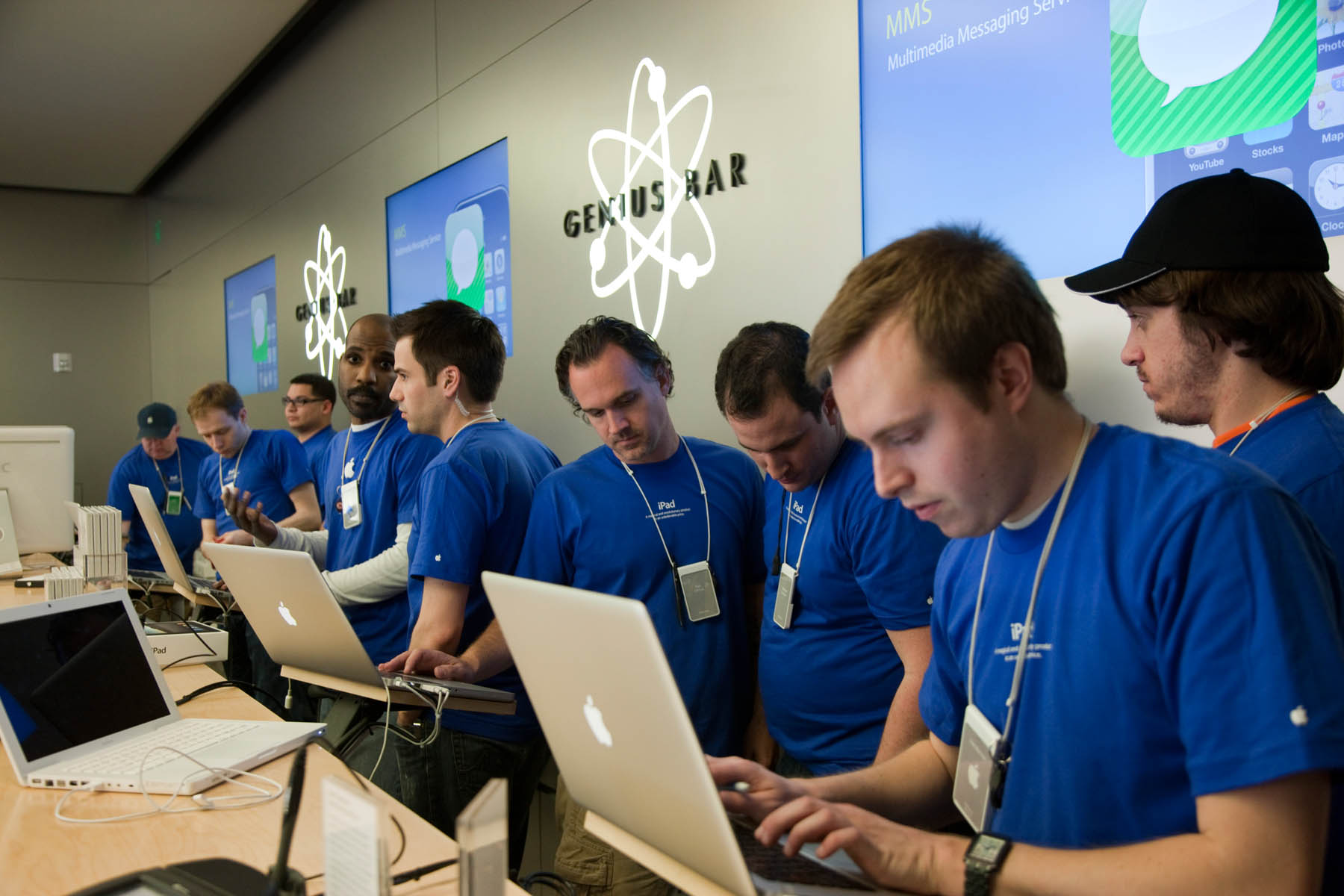 Apple employees work behind the Genius Bar at the Apple store in Bethesda, MD.