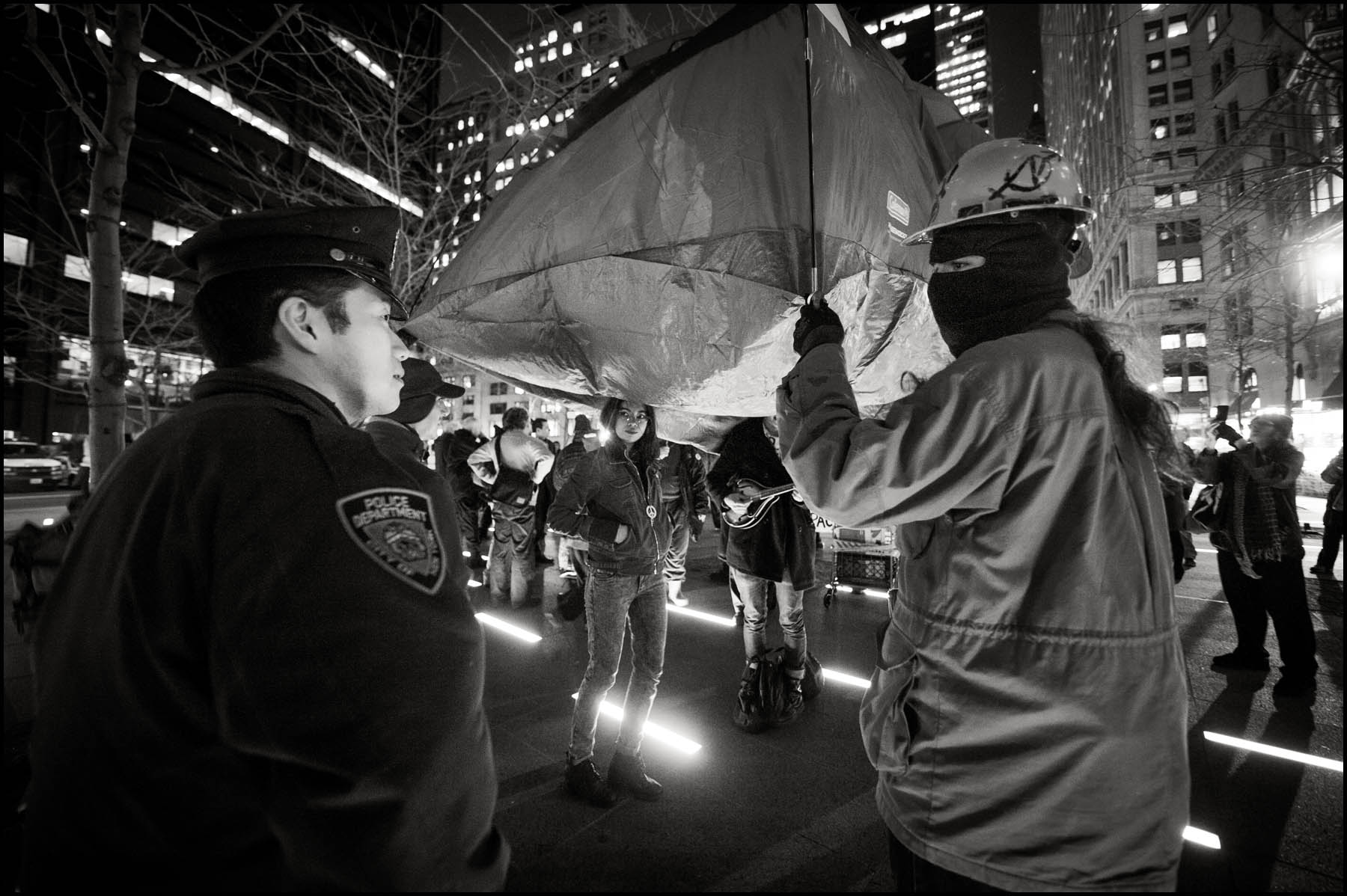 Protesters try to stick to the letter of the law by holding their tent and not setting it down after Zuccotti Park was cleared by police.