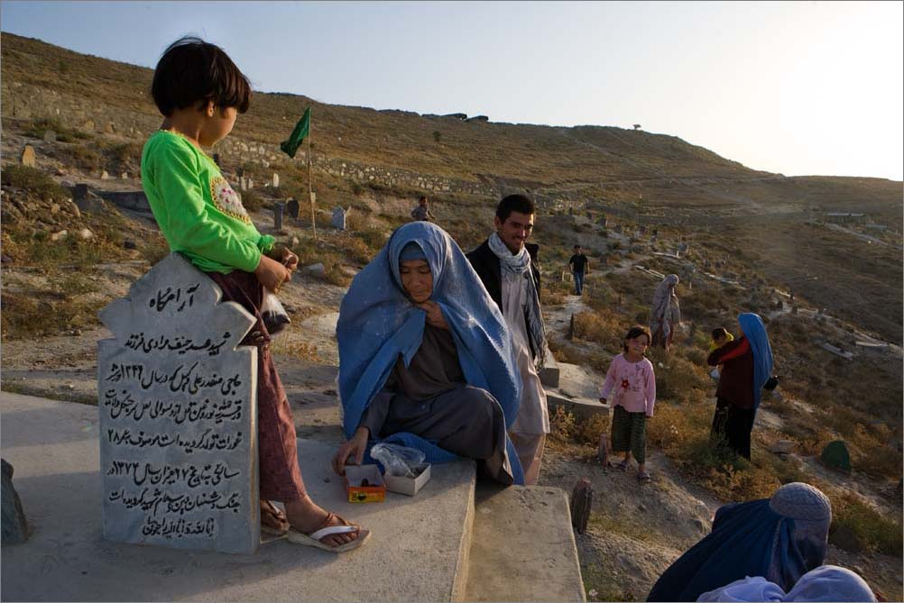 A family gathers in a graveyard next to the Russian pool in Kabul, Afghanistan, to honor the dead on Friday, the Muslim holy day, August 2009.
