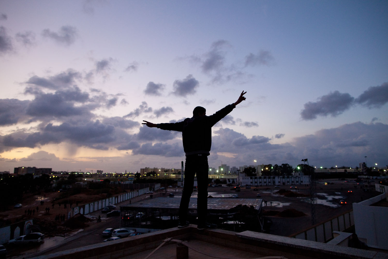 A boy stands on the roof of one of Muammar Gaddafi's old palaces in Benghazi, burned down by the opposition forces.