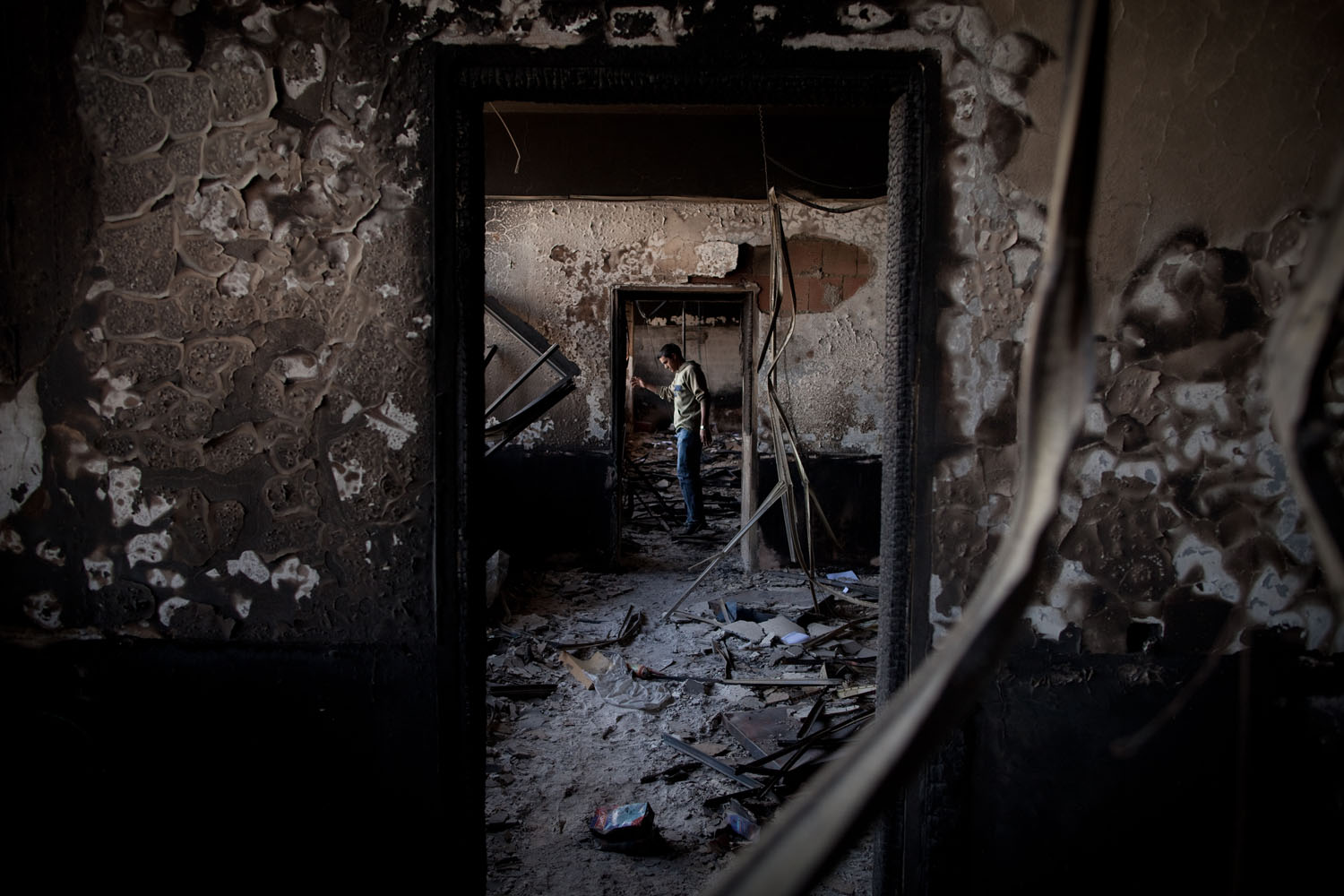 A man walks through a destroyed government complex that was ransacked and burned by the opposition.