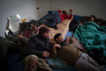 Opposition fighters wake at dawn in a small building at the rebel-held checkpoint near the Ras Lanuf oil refinery.
