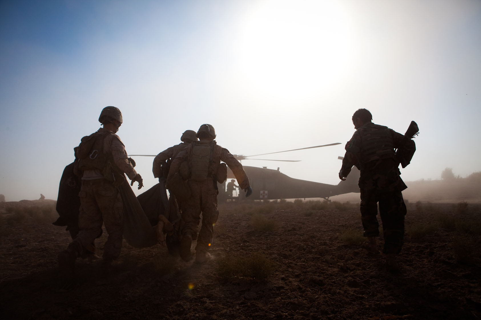 Marines and an Afghan National Army soldier carry an Afghan civilian wounded by insurgent gunfire on a stretcher to a waiting medevac helicopter in southern Helmand Province, Afghanistan, November 22, 2010.