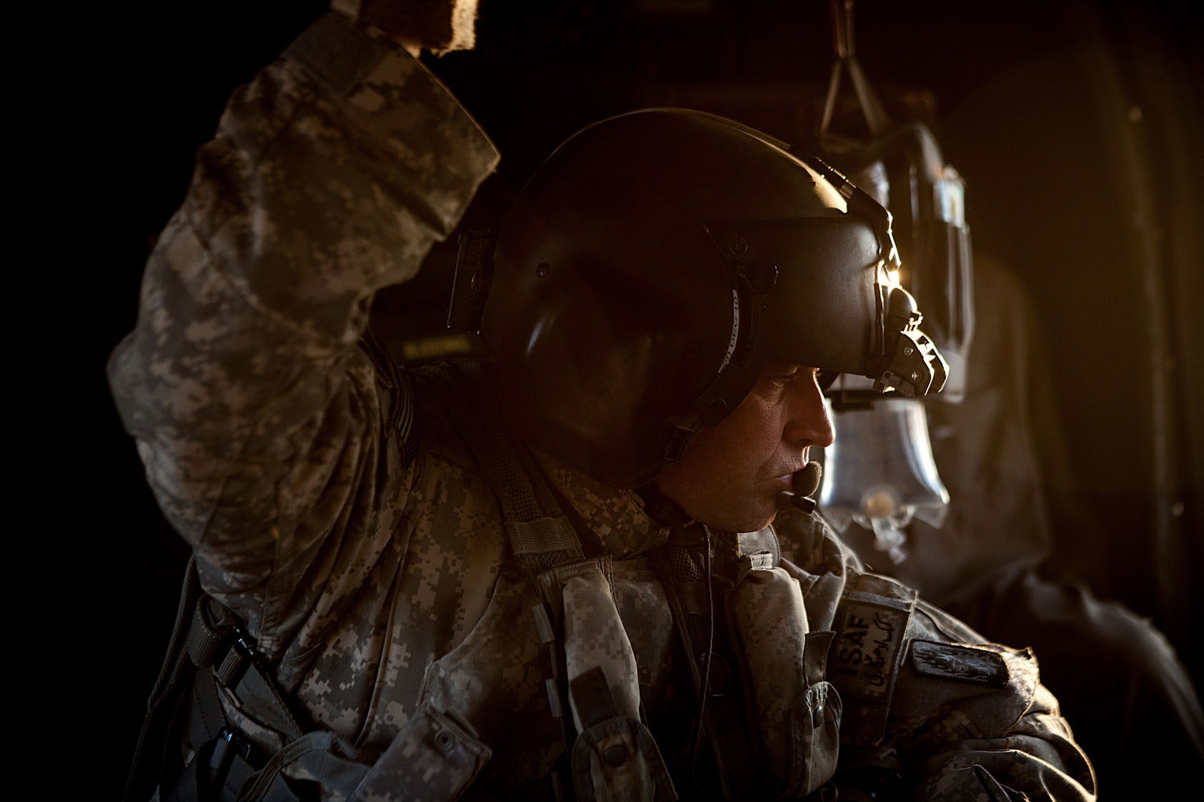 Staff Sergeant Christopher Meece, a crew chief in a United States Army's Dustoff medevac team, looks out from the window of a Black Hawk helicopter, Helmand Province, Afghanistan, November 24, 2010.