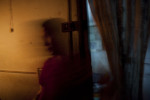 A woman walks through a curtain from her home, which has electricity from a small generator, to her roadside restaurant, lit only by candles.