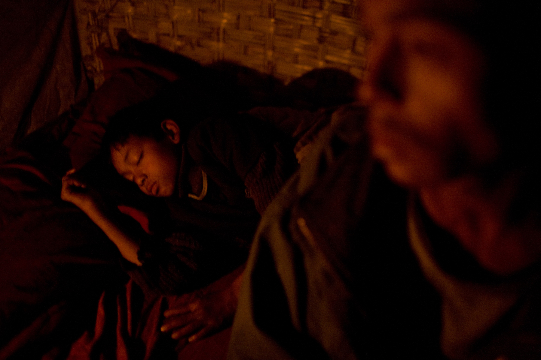 A young boy sleeps next to his father in their home in Kathmandu.