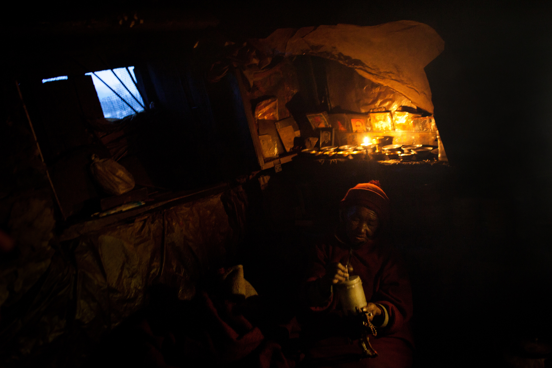 An elderly nun living in Thame prays by the candlelight cast by the small shrine above her bed.