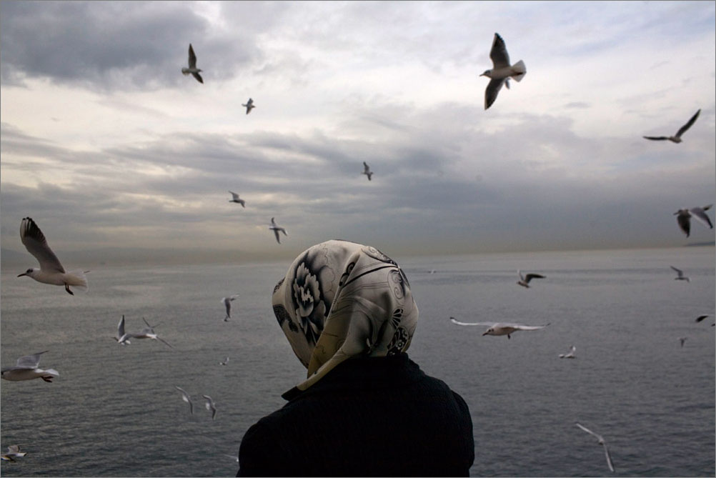 Waiting on the ferry, a woman looks out on the Aegean Sea, February 2009.