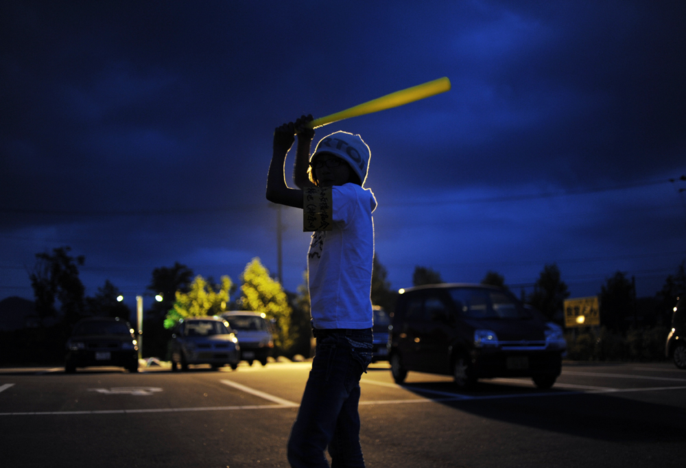Rukiya Hara (12) impersonates a baseball player of  Yomiuri Giants ,Alex Ramírez, at the parking lot of Ichinoseki, Iwate prefecture. Rukiya's favorite baseball team is the Softbank Hawks though, not the Tokyo Yomiuri Giants because the Softbank team is based in Fukuoka, Kyusyu, where he was born.  He and his father, Takaki Hara (38) are on the way back home from the Tohoku region where the 3.11's M9 earthquake and Tsunami devastated and the road trip of Takaki Hara's NPO and personal mission. June 13, 2011.