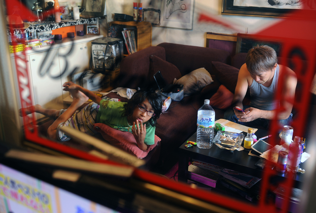 Takaki Hara (38) is absorbed in his cell phone text messaging while his son, Rukiya (12) watches TV in their living room. They are reflected on the mirror of Budweiser goods. Rukiya is on summer break. August 13, 2011.