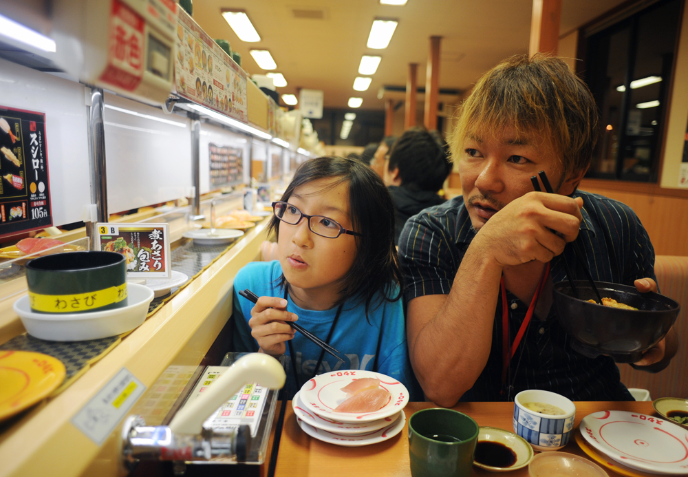 Takaki Hara (38) right, and his son Rukiya (12), left, waits for sushi plates to be delivered patiently at restaurant in Ichinoseki, Iwate prefecture. They are on the way back home from the Tohoku region where the 3.11's M9 earthquake and Tsunami devastated for volunteering and research on the newly displaced single parent families due to the 3.11 earthquake as part of Takaki Hara's NPO and personal mission.  June 13, 2011.