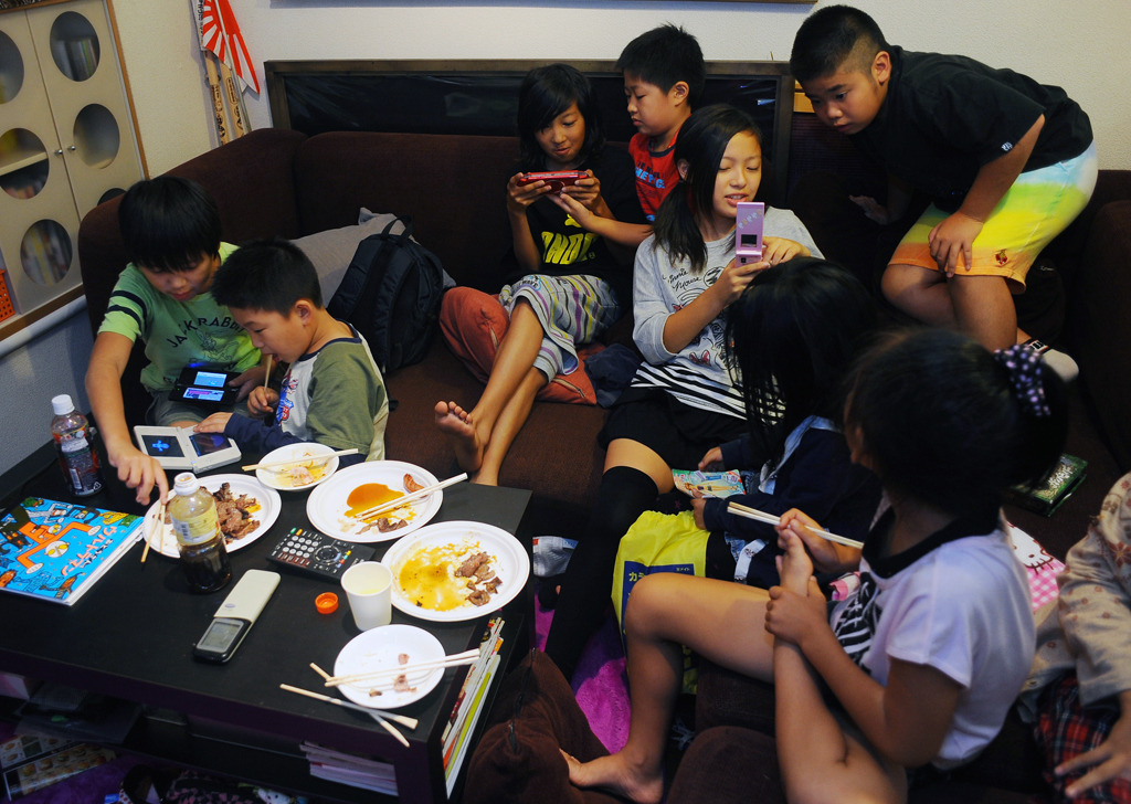 Rukiya Hara (12) ,center,and his friends, all children of single parents are absorbed in Playstation game and other electrical gadgets at his home BBQ party held for Takaki Hara's Single Family NPO members.  Kawasaki-city, kanagawa prefecture. October 1, 2011.