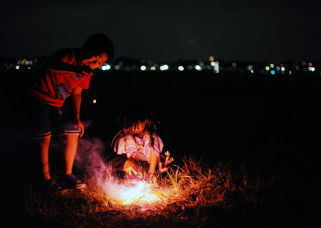 Rukiya Hara(12),right, and his friend, Tomoki Koga(9) ,left, also a child of single mother, have fun with short lived toy fireworks in their own way on the shore of Tama river in Kanagawa prefecture at night. October 1, 2011.