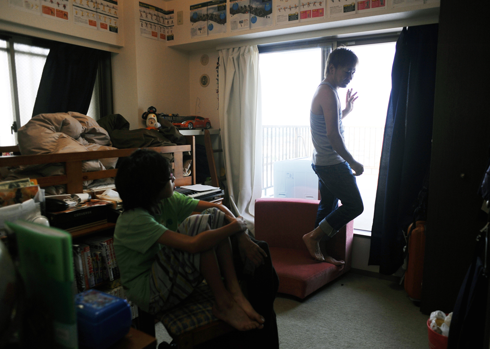 Takaki Hara (38),right, becomes a bit upset about his son Rukiya's disorganized room because Rukiya (12), left,is on summer break and starts leading a loose life.  Kawasaki city, kanagawa prefecture. August 13, 2011.
