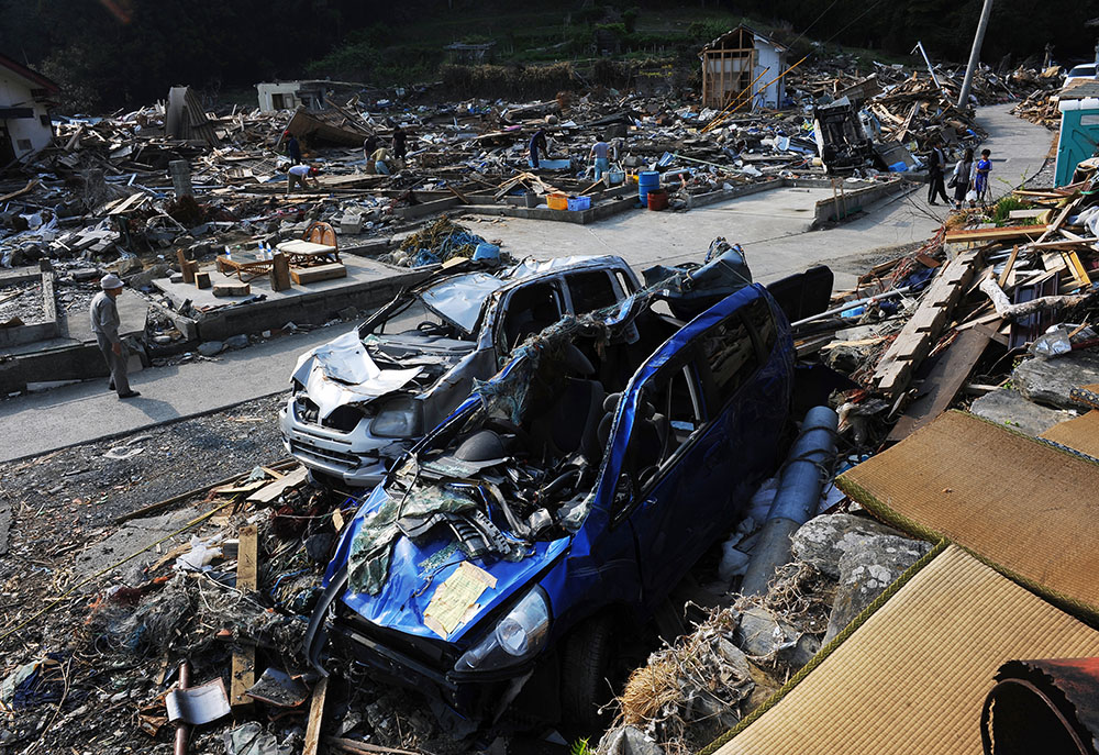 Villagers walk through tsunami damaged wreckage at Hamagurihama in Ishinomaki, Miyagi prefecture.