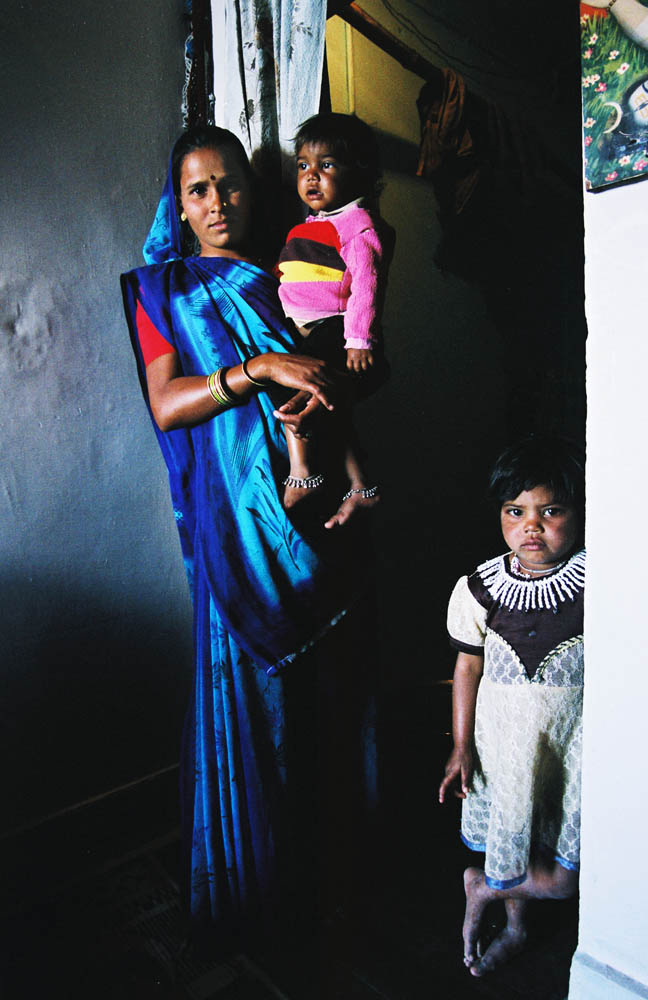 Bhawana,24, holds her daughter, Gaurav,2,with an elder sister Sunny,4,who also suffers from the contaminated water,standing by.