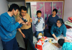 Li Chuan-hua shows and gives his souvenirs from Japan including sony handycam recorder to his friend, Gao Bo (33) and Li Chuan-hua's nephew, Wu Fan(8), center, at apartment of his mother-in-law, Ren Ji-lan (60), far right. Lin Yi-City, Shandong Province, China.