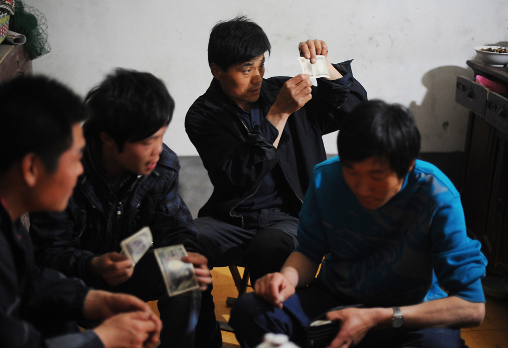 Li Chuan-sheng (33), cousin of Li Chuan-hua  examines Japanese paper money at Li Chuan-hua's mother's house. Lin Yi-City Shandong Province, China.