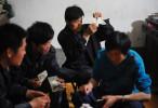 Li Chuan-sheng (33), cousin of Li Chuan-hua  examines Japanese paper money at Li Chuan-hua's mother's house. Lin Yi-City Shandong Province, China.
