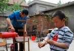 Li Chuan-hua washes his hair while his son, Li Jia-yi (5), plays with his watch at the courtyard of their house. The house hasn't had a sewage disposal system connected yet. So there are no shower facility or running toilet available.  Lin Yi-City, Shandong Province, China.