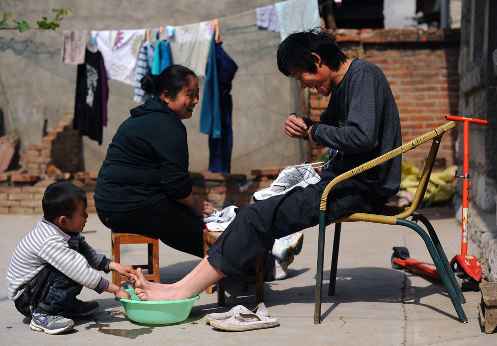 Li Chuan-hua and his wife, Wu Yan(32) wash Li's newly bought shoes while his son Li Jia-yi looks over in the courtyard of their house. Lin Yi-City, Shandong Province, China.