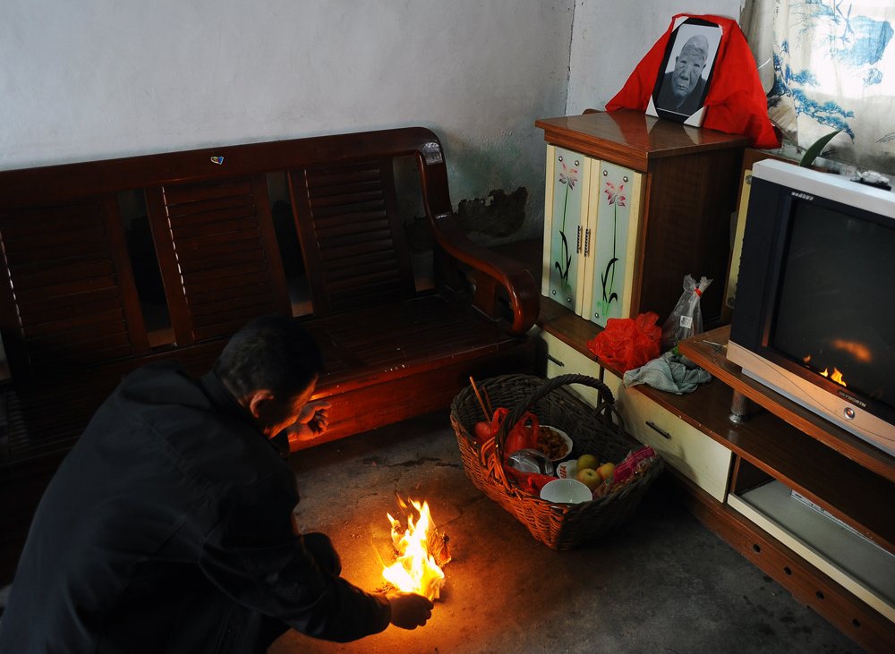 Li Chuan-hua's father, Li Shi-de, passed away due to a stroke at the age of 73, just on the day before he arrived home from Japan※. Li Chuan-hua's elder brother, Li Chuan-zeng (42), helds a memorial service for the seventh day anniversary at home. Lin Yi-City Shandong Province, China. ※Li Chuan-hua's family kept the news untill he came back home. He refused to be photographed when he heard the news and collapsed. I have started taking photos of the funeral with his permission to do so since the memorial service for the seventh day anniversary of his father's death.
