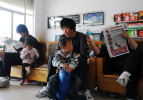 Li Chuan-hua waits for his haircut at a local barbershop with his son and wife. He has often been oblivious to others since his father passed away. Lin Yi-City, Shandong Province, China.