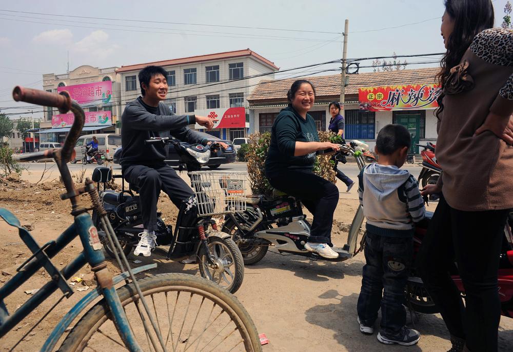 Li Chuan-hua, his wife, Wu Yan, and his son, Li Jia-yi (5), hang around with Wu's friend at downtown of Lin Yi-City, Shandong Province, China.