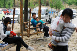 Li Chuan-hua babysits his son Li Jia-yi at a rest place of parking lot. Although Li Jia-yi is already five years old, he behaves like a spoiled child because he hasn't seen his father for almost three years. Li Chuan-hua and his friends are on a family day trip. Shandong Province, China.