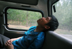 Li Chuan-hua falls asleep deeply in the backseat of his friend's car. He is exhausted from one-day family excursion with his friend's family. Shandong Province, China.